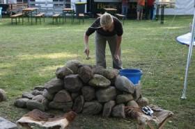 Zum späteren Brennen der Perlen wird ein Freilandofen aus Feldsteinen und Ton aufgebaut.